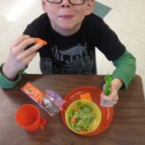 Logan Smith enjoys a salad during snack time at Sawtooth Elementary School in Grand Marais, Minn. Logan's class grew the lettuce throughout the winter using tower gardens in his classroom. Photo courtesy of Betsy Jorgenson.